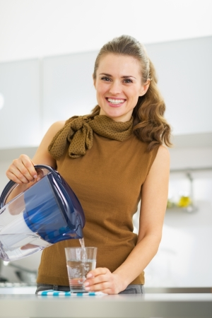 Photo pour Smiling young housewife pouring water into glass from water filter pitcher - image libre de droit
