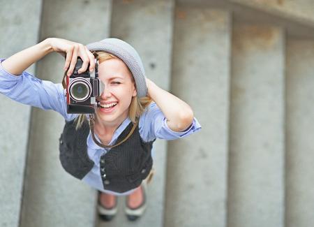 Foto de Happy hipster girl making photo with retro camera on city street - Imagen libre de derechos