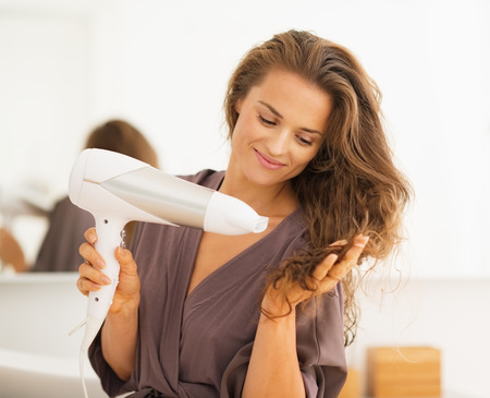 Foto de Happy young woman blow drying hair in bathroom - Imagen libre de derechos