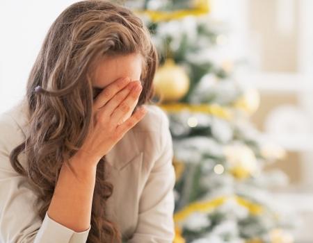 Foto de Stressed young woman in front of christmas tree - Imagen libre de derechos