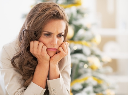 Photo pour Portrait of frustrated young woman near christmas tree - image libre de droit