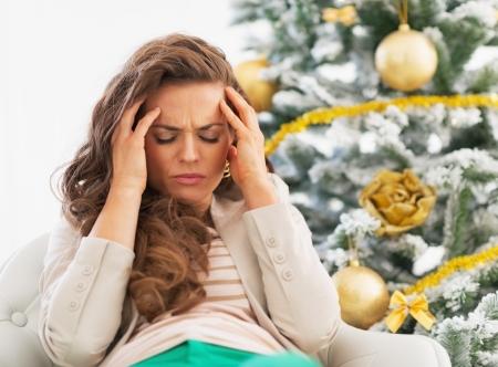 Foto de Portrait of frustrated young woman near christmas tree - Imagen libre de derechos