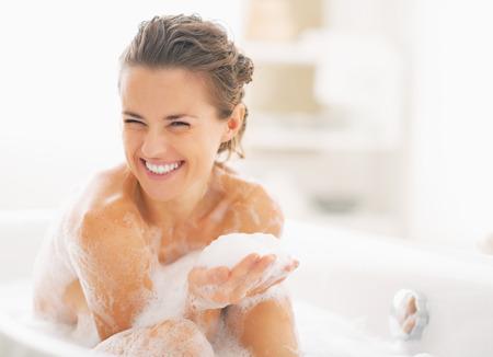 Photo pour Portrait of happy young woman playing with foam in bathtub - image libre de droit