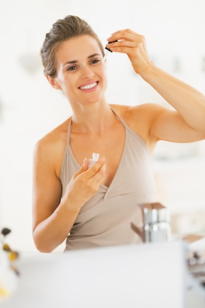 Photo pour Young woman applying cosmetic serum in bathroom - image libre de droit