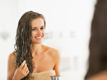 Photo pour Happy young woman applying hair mask in bathroom - image libre de droit