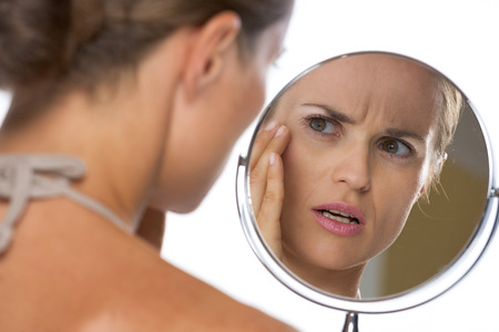 Photo for Concerned young woman looking in mirror - Royalty Free Image
