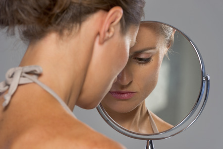 Photo pour Stressed young woman looking in mirror - image libre de droit