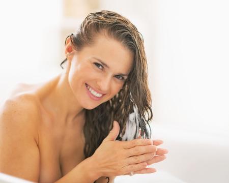 Photo pour Happy young woman applying hair conditioner - image libre de droit