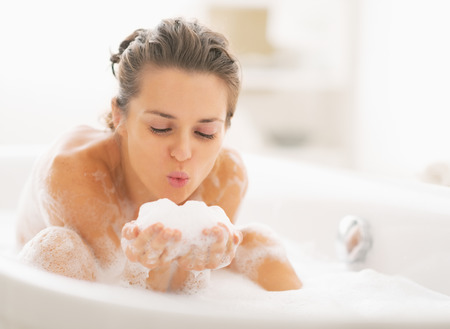 Photo pour Young woman playing with foam in bathtub - image libre de droit