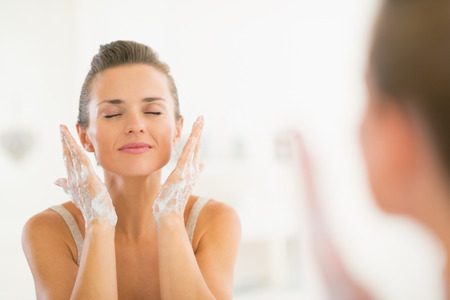 Photo pour Young woman washing face in bathroom - image libre de droit