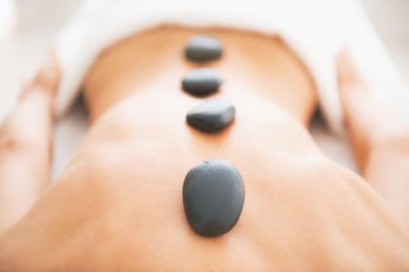 Photo pour Closeup on young woman receiving hot stone massage - image libre de droit