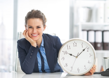 Photo pour Happy business woman showing clock - image libre de droit