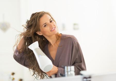 Photo pour Happy young woman blow drying hair in bathroom - image libre de droit