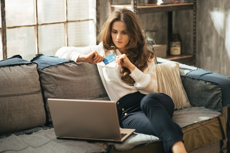 Photo pour Young woman with credit card using laptop in loft apartment - image libre de droit