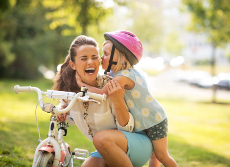 Photo for Happy mother and baby girl having fun in park with bicycle - Royalty Free Image
