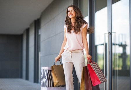 Photo pour Young woman with shopping bags walking out from shop - image libre de droit