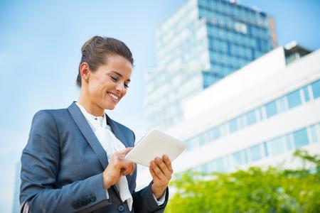 Photo pour Business woman with tablet pc in office district - image libre de droit