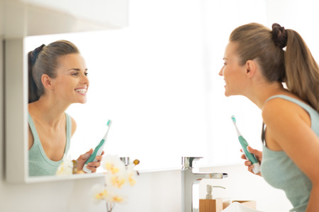 Foto de Young woman looking in mirror after brushing teeth - Imagen libre de derechos