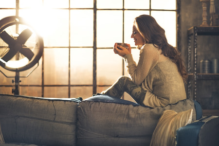 Foto de Young woman enjoying cup of hot beverage in loft apartment - Imagen libre de derechos