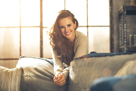 Photo pour Portrait of happy young woman in loft apartment - image libre de droit