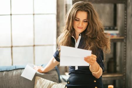 Foto de Young woman reading letter in loft apartment - Imagen libre de derechos
