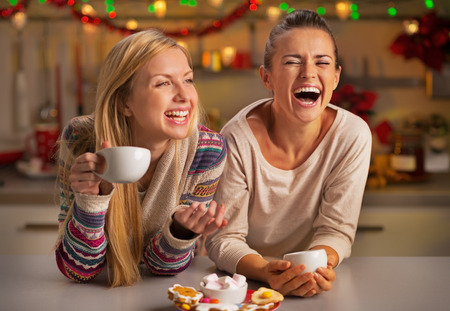 Foto de Portrait of laughing girlfriends having christmas snacks in christmas decorated kitchen - Imagen libre de derechos