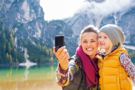 Photo for Happy mother and baby making selfie on lake braies in south tyrol, italy - Royalty Free Image