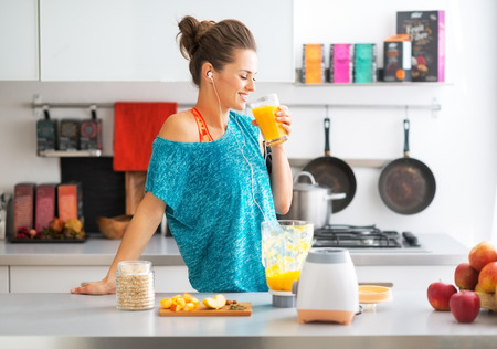 Photo pour Happy fitness young woman drinking pumpkin smoothie in kitchen - image libre de droit