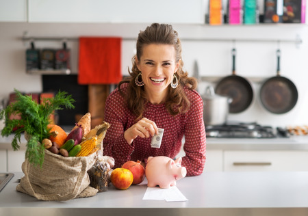 Foto de Portrait of happy young housewife putting money into piggy bank after shopping on local market - Imagen libre de derechos