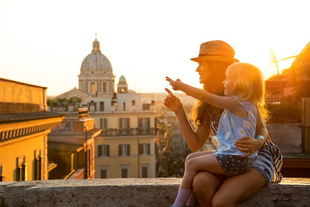 Photo pour Mother and baby girl sitting on street overlooking rooftops of rome on sunset and pointing - image libre de droit