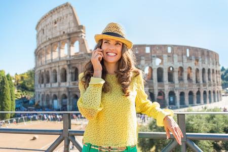 Foto de Happy young woman talking cell phone in front of colosseum in rome, italy - Imagen libre de derechos
