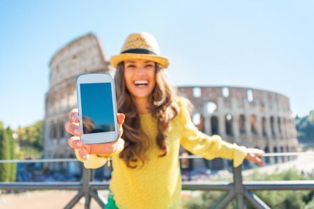 Photo for Closeup on happy young woman showing cell phone in front of colosseum in rome, italy - Royalty Free Image
