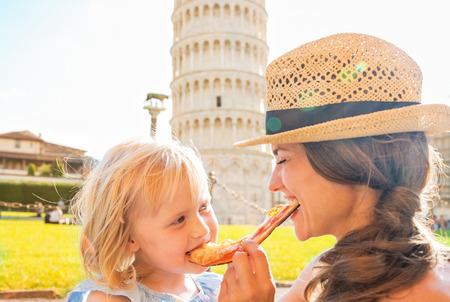 Foto de Happy mother and baby girl eating pizza in front of leaning tower of pisa, tuscany, italy - Imagen libre de derechos