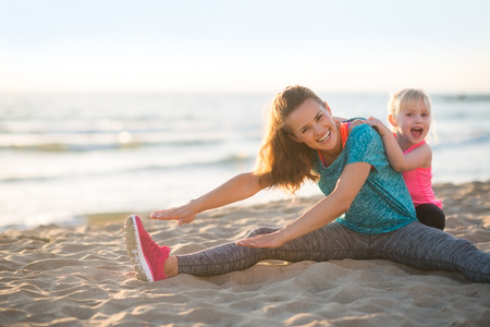 Foto für Healthy mother and baby girl stretching on beach in the evening - Lizenzfreies Bild
