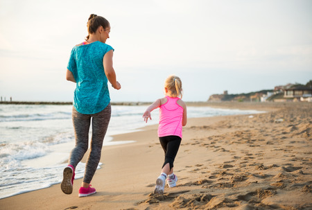 Foto de Healthy mother and baby girl running on beach. rear view - Imagen libre de derechos