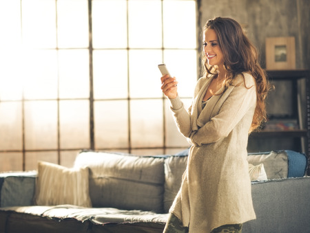 Photo pour Seen in profile, a brunette woman in comfortable clothing is standing in a loft living room, looking down at her phone and smiling. Urban chic loft decoration details and window. - image libre de droit