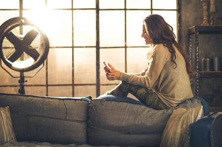Foto per Seen from the side,a brunette woman is smiling, looking down at her phone sitting on the back of a sofa. Industrial chic ambiance and cozy atmosphere, sunlight is streaming through the loft window. - Immagine Royalty Free