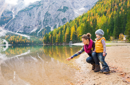 Foto de A mother, kneeling next to her daughter on the shores of Lake Bries, is pointing into the water. The colours of their hiking gear reflect the autumn foliage. - Imagen libre de derechos