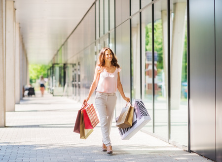 Photo pour A brown-haired woman wearing muted, gentle colours holds five colourful, patterned shopping bags walks towards the doors of an exclusive shopping mall. Her smile and stance show a confident, strong, happy woman with the means to spend money on herself.  T - image libre de droit