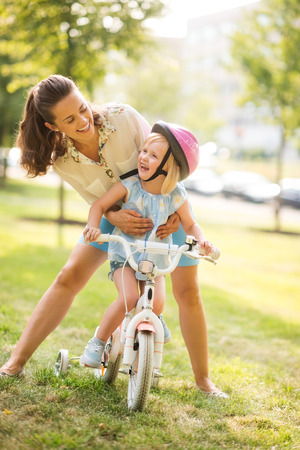 Photo pour A mother hugs her daughter from behind, as the daughter wearing a pink helmet looks up towards her mother, laughing and proud. She has just learned to ride her bike by herself, and is proud of herself. - image libre de droit