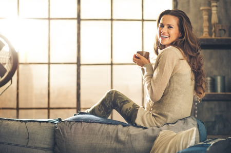 Photo for A brunette long-haired woman is seen from the side while sitting on the back of a sofa. She  is smiling and holding a hot cup of coffee. Industrial chic background, and cozy atmosphere. - Royalty Free Image