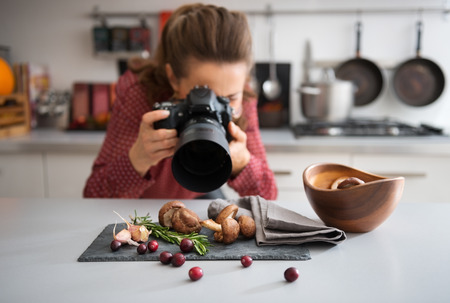 Foto de A woman food photographer in the background leans down to take a close-up, in a modern kitchen, of autumn fruits and vegetables - mushrooms, garlic, rosemary, and cranberries. - Imagen libre de derechos