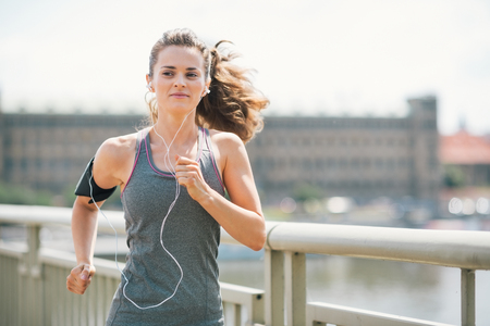 Photo pour An athletic woman is jogging on a bridge, listening to music. Her long hair is up in a ponytail and blowing in the wind. - image libre de droit