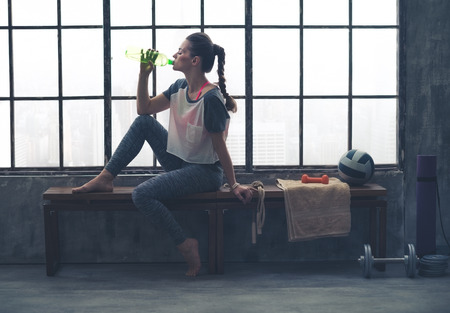 Photo for Fit woman in profile sitting on bench in loft gym drinking water. After a good workout, it's important to hydrate. - Royalty Free Image