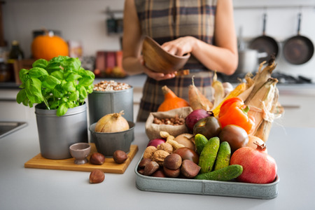 Photo pour A tray full of Autumn fruits, nuts, and vegetables sits on a kitchen counter. Next to the tray, a wooden cutting board featuring a fresh basil plant and onion promise a delicious meal ahead. - image libre de droit