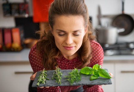 Foto de Oh, the heady smell of fresh herbs, conjuring up dreams of all kinds of recipes... A woman, smelling deeply, and closing her eyes in pleasure, leans over a slate showing a few sprigs of fresh herbs. - Imagen libre de derechos