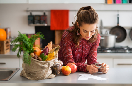 Photo pour An elegant woman is reading the shopping lists on her kitchen counter. Next to her on the kitchen counter, a burlap sac holds a wide variety of fall fruits and vegetables. - image libre de droit