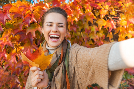 Foto de Portrait of cheerful young woman with autumn leafs in front of foliage making selfie - Imagen libre de derechos