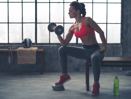 Photo for Feel that burn! A fit, sporty young woman is sitting in profile on a bench in profile, lifting weights with one hand, while resting her elbow on her knee. - Royalty Free Image