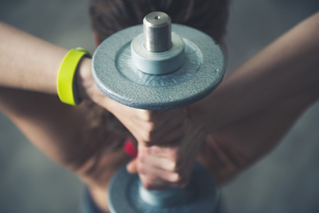 Foto de Body and mind workout in loft fitness studio. Fitness woman holding dumbbell behind head. Close up - Imagen libre de derechos